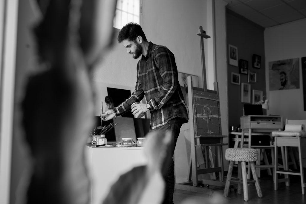 Jean Carlos Puerto en su estudio concentrado en el proceso para pintar.