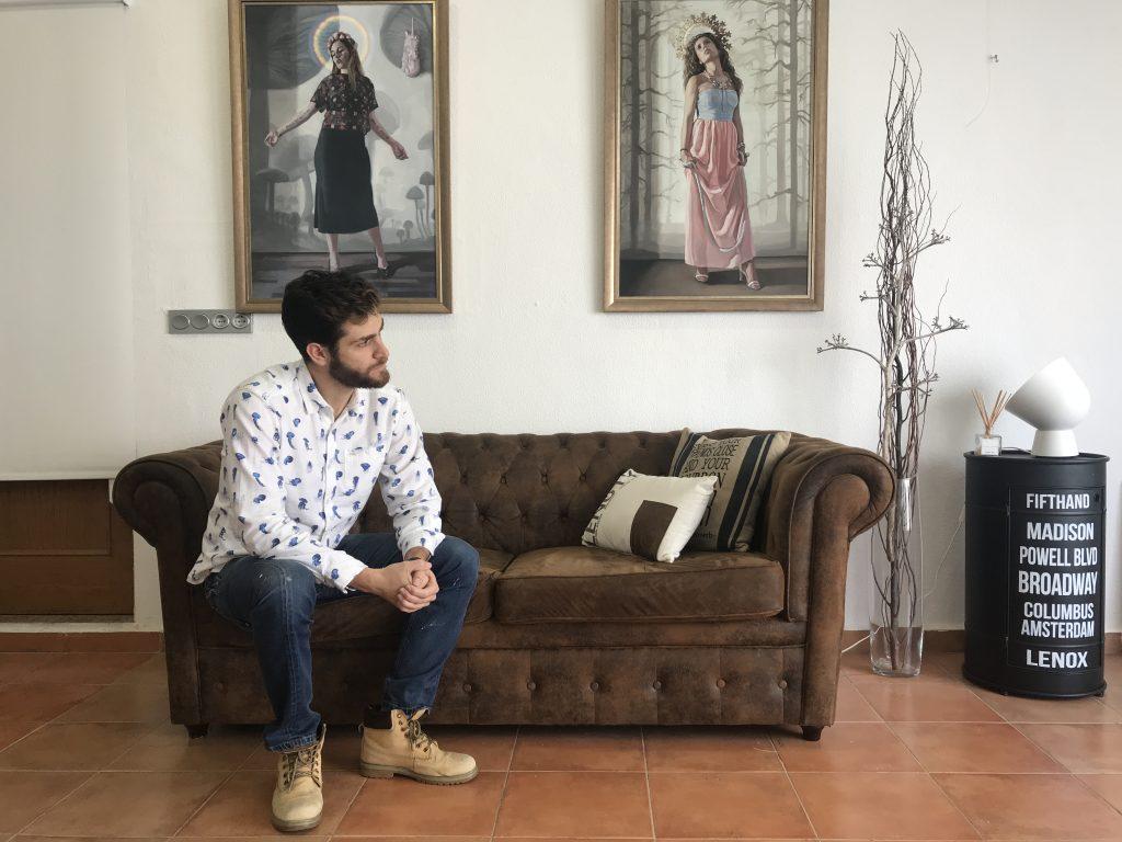 Imagen que muestra a Jean Carlos Puerto en su estudio sentado en un sillón de perfil. psicología murcia. Al fondo dos cuadros.